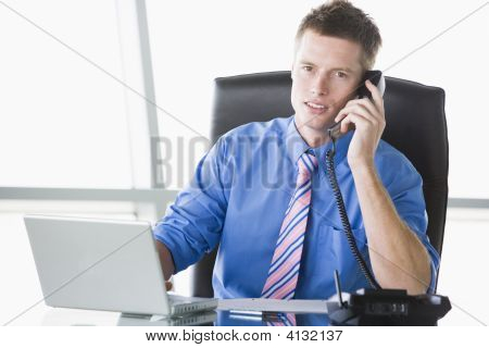 Businessman Sitting In Office With Laptop Using Telephone