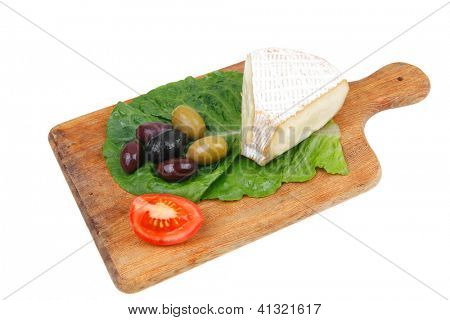 brie cheese on wooden platter with olives and tomato isolated over white background