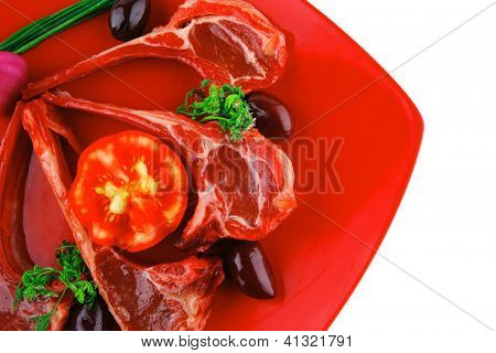 ribs served on red plate with tomatoes adn greenery