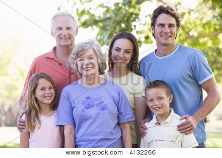 Extended Families Standing In Park Smiling
