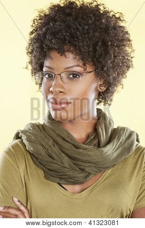 Portrait of a smart African American woman wearing glasses with a stole round her neck over colored background