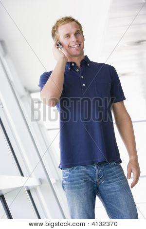 Man Standing In Corridor Wearing Headset Smiling