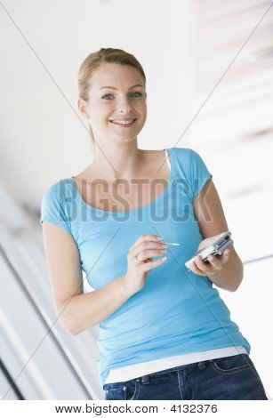 Woman Standing In Corridor Using Personal Digital Assistant Smiling
