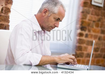 Businessman Sitting In Office Typing On Laptop