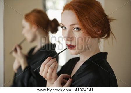 Portrait of a redheaded woman applying lip liner