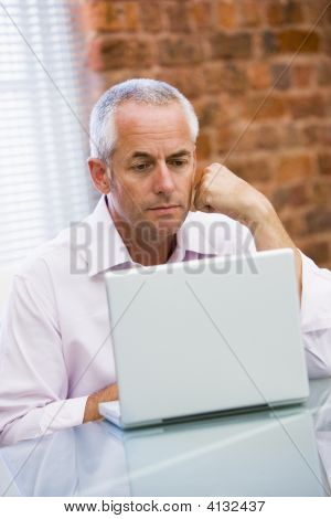 Businessman Sitting In Office On Laptop