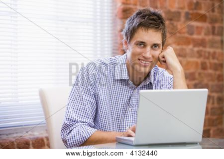 Businessman Sitting In Office With Laptop Smiling