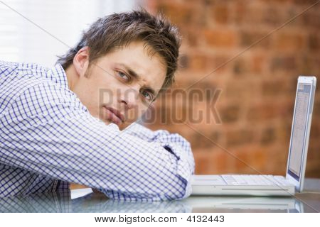 Businessman Sitting In Office With Laptop Looking Unhappy