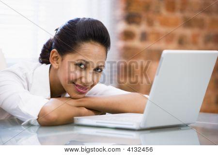geschäftsfrau in Office mit Laptop lächelnd