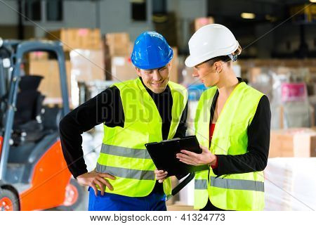 Worker or warehouseman and his coworker with clipboard at warehouse of freight forwarding company, pointing