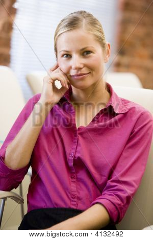 Businesswoman Sitting In Office Space Smiling