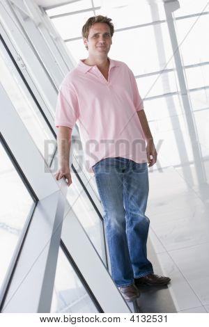 Man Standing In Corridor Smiling