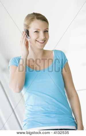 Woman Standing In Corridor Wearing Headset And Smiling