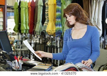 Bella joven mirando un papel mientras selecciona la muestra textil en tienda