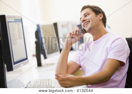 Man Sitting In Computer Room Using Cellular Phone And Smiling