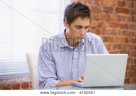 Businessman In Office Typing On Laptop