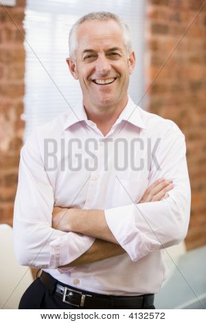 Businessman Standing In Office Laughing