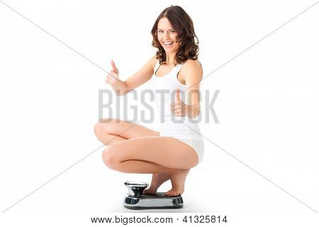 Diet and weight, young woman sitting on her haunches on a scale, she is happy about the success