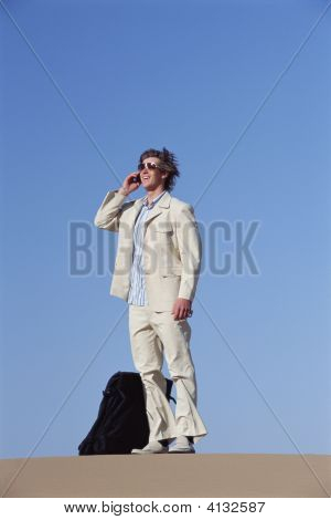 Homem ao ar livre com mala usando telefone celular