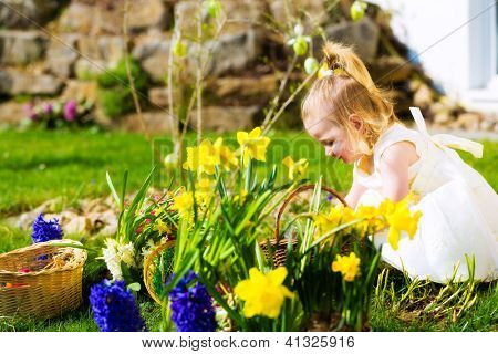 Little Girl on an Easter Egg hunt on a meadow in spring, she has found an Easter egg