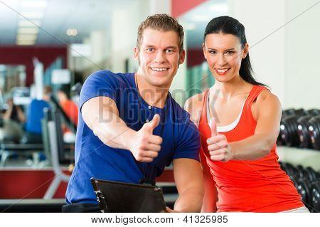 Mujer con su entrenador personal de fitness en el gimnasio, hacer ejercicio con pesas