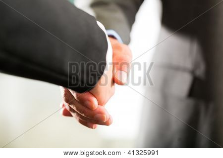 Two businesspoeple shaking hands closing a deal, closeup