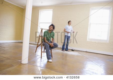 Two Men In Empty Space With Ladder Holding Paper