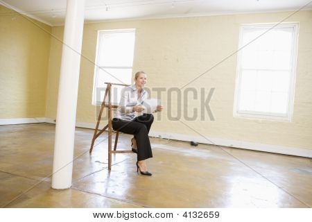 Woman Sitting On Ladder In Empty Space Holding Paper Smiling