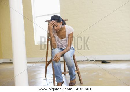 Woman Sitting On Ladder In Empty Space Looking Tired