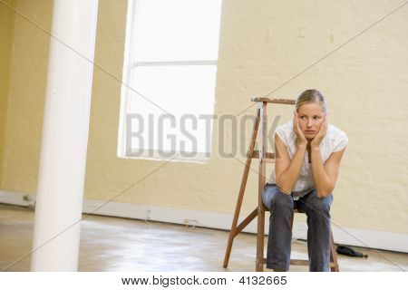 Woman Sitting On Ladder In Empty Space Looking Bored