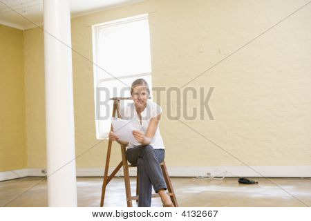 Woman Sitting On Ladder In Empty Space Holding Paper
