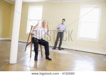 Two Men With Ladder In Empty Space Making Plans For Room