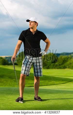 Young sportive man playing golf on a course, he might play a golf tournament