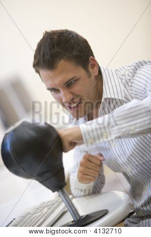 Man Sitting In Computer Room Using Small Punching Bag For Stress Relief