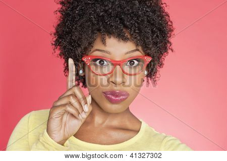 Portrait of an African American woman in retro glasses pointing upward over colored background
