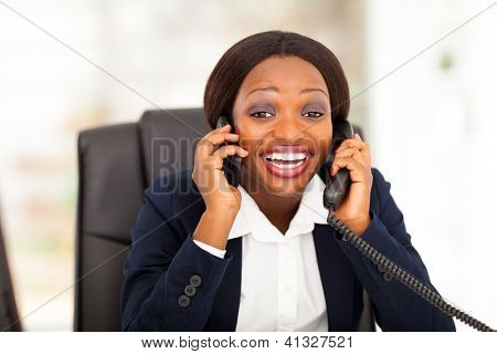 funny african american businesswoman talking on landline and mobile phone at same time