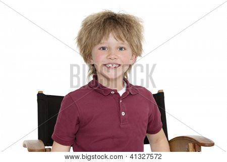 Retrato de um menino de escola feliz sentado na cadeira de diretor sobre fundo branco