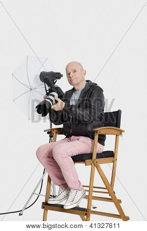 Middle age photographer sitting on director's chair with camera