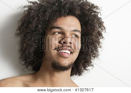 Close-up of a happy young man with curly hair looking away over white background