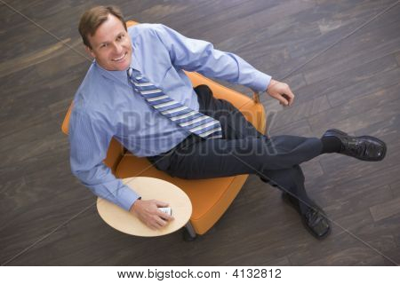Businessman Sitting Indoors With Cellular Phone Smiling