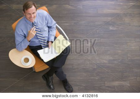 Businessman Sitting Indoors With Coffee And Folder Smiling