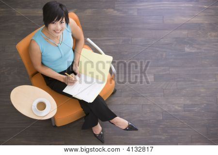 Businesswoman Sitting Indoors With Coffee And Folder Smiling