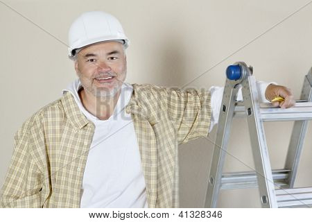 Portrait of a happy male contractor over colored background