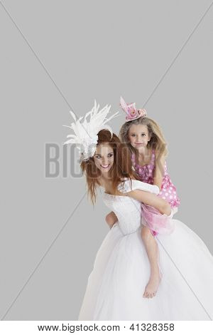 Bridesmaid getting a piggyback ride from young bride over gray background