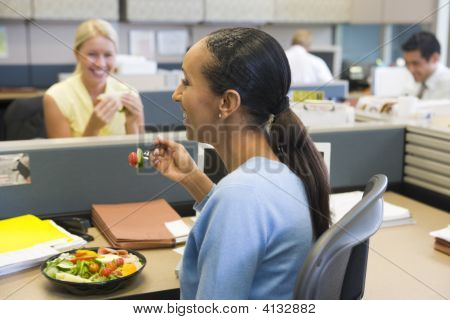 Businesswoman In Cubicle Eating Salad And Smiling