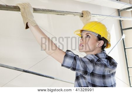 Woman worker placing rod on scaffold at construction site