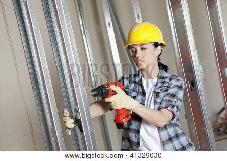 Young worker drilling at construction site