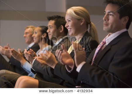 Five Businesspeople Applauding And Smiling In Presentation Room