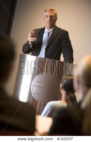 Businessman Giving Presentation At Podium