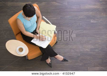 Businesswoman Sitting Indoors With Coffee And Folder